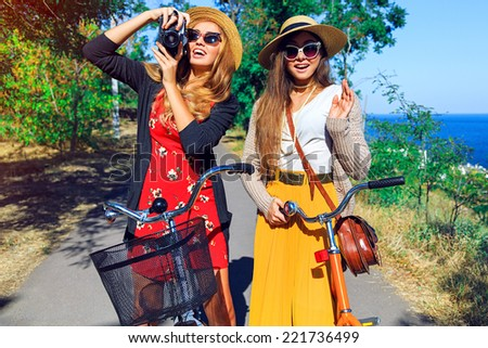 Outdoor fashion lifestyle portrait of two pretty smiling peat friends girls, walking near sea side have perfect  free vacation day together, taking pictures an retro camera, wearing vintage clothes. - stock photo