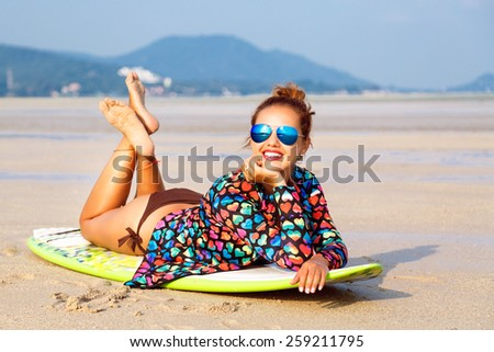 Outdoor fashion lifestyle summer portrait of stunning sexy surfer woman, wearing bright outfit makeup and sunglasses. Laying on surfboard, amazing view on mountains and empty beach. - stock photo