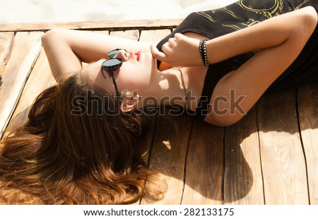 Outdoor fashion look of young woman wearing summer sunglasses,laying and laughing on the beach of sand,having sunbath.Wear summer bright outfit,vintage summer outfit colors.Hipster teenager girl - stock photo
