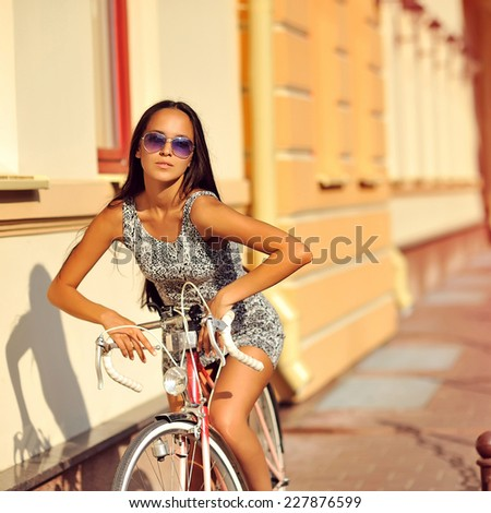 Outdoor fashion portrait of a beautiful brunette girl with bicycle - stock photo