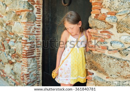 Outdoor fashion portrait of a cute little girl wearing yellow dress and bag - stock photo