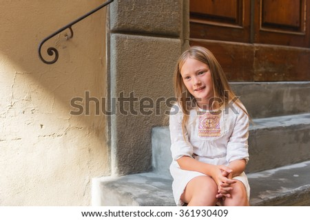 Outdoor fashion portrait of a pretty little girl, wearing white dress  - stock photo