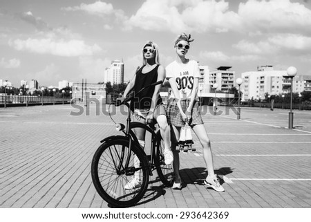 Outdoor fashion portrait of attractive young women with bicycle and roller skates. Two teen swag girls. black white toned - stock photo
