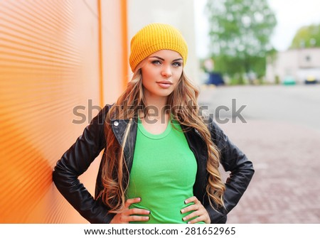 Outdoor fashion portrait of beautiful blonde woman wearing a black rock leather jacket and hat in the city - stock photo