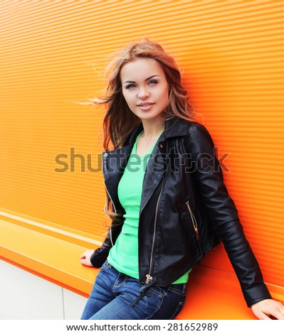 Outdoor fashion portrait of beautiful blonde woman wearing a black rock leather jacket in the city - stock photo