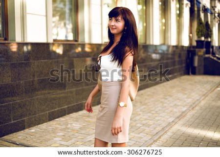 Outdoor fashion portrait of elegant brunette woman, classic style, soft beige colors, young business woman walking on the street, toned warm colors. - stock photo