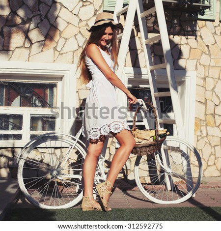 Outdoor fashion portrait of elegant lady standing near hipster retro bicycle in vintage stylish dress and hat. enjoy and having fun fall autumn day in the city with a retro instagram filters - stock photo