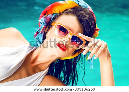 Outdoor fashion portrait of glamour lady enjoying her vacation on luxury pool on hot tropical island,hot summer fashion accessory,stylish sunglasses,bikini.Sexy perfect fit body woman.red lips,party  - stock photo