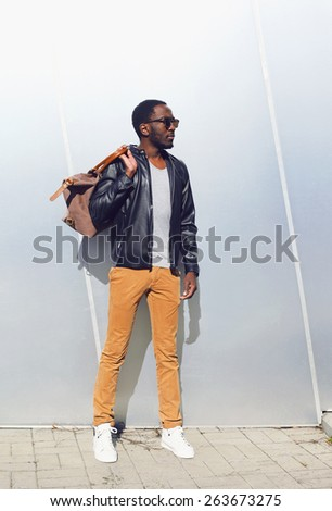 Outdoor fashion portrait of handsome african man in black leather jacket with bag standing against the shiny metal wall - stock photo