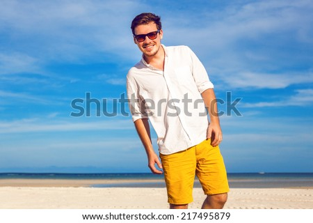 Outdoor fashion portrait of handsome man posing at amazing tropical beach, in nice sunny day, beautiful view on blue sky and ocean, wearing casual yellow sorts classic white shirt and sunglasses. - stock photo