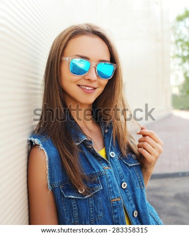 Outdoor fashion portrait of pretty girl in the sunglasses and jeans clothes - stock photo