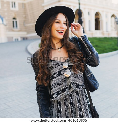 Outdoor fashion portrait of pretty stylish  laughing  woman in black wool hat. leather jacket, overall , bright make up, red lips. European street background. Street look. Enjoy weekends.  Having fun. - stock photo