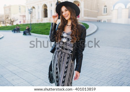 Outdoor fashion portrait of pretty stylish  laughing  woman in black wool hat. leather jacket, overall , bright make up, red lips.  European street background. Street look. Enjoy weekends.  - stock photo
