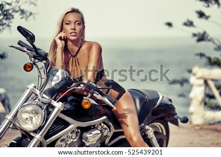 Outdoor fashion portrait of pretty young woman in bikini on a motorcycle