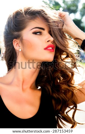 Outdoor fashion portrait of sexy sensual model girl with perfect curled brunette hair,amazing make-up,posing opposite the sunset,Fresh and young face,glowing skin,summer accessories,fashion style - stock photo