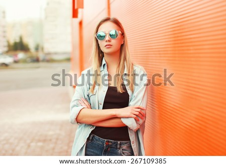 Outdoor fashion portrait of stylish woman in sunglasses against a colorful urban wall - stock photo