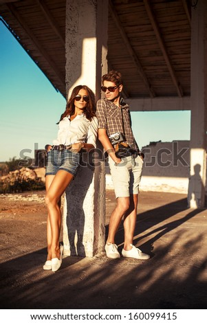 Outdoor fashion portrait of young beautiful couple in summer posing outdoor. - stock photo
