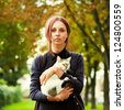 Outdoor fashion Portrait of young beautiful woman with little cat - stock photo