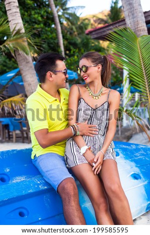 Outdoor fashion portrait of young couple in love sitting on kayak boats, in exotic hot tropical country, speaking to each other joking and enjoy traveling together. - stock photo