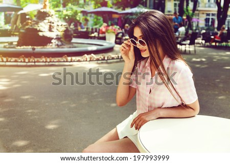 Outdoor fashion portrait of young pretty brunette sitting alone at old city cafe and waiting for her boyfriend wearing retro white outfit and round sunglasses. - stock photo
