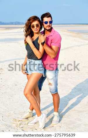 Outdoor fashion portrait of young pretty couple in love posing at amazing beach, wearing bright stylish casual clothes and sunglasses, enjoy their summer vacation near ocean. - stock photo