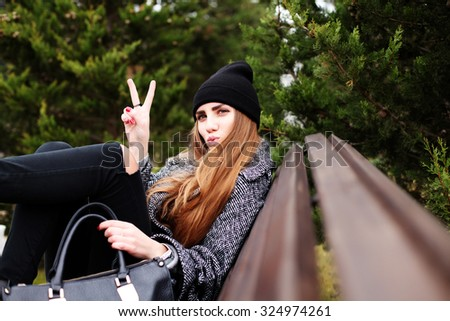 Outdoor fashion portrait of young pretty funny girl wearing trendy fall outfit, black hat, grey coat and leather bag. Cold season. Warm clothes. Young happy woman having fun outdoor - stock photo