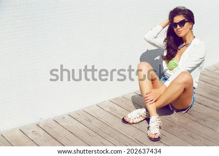 Outdoor fashion portrait of young pretty woman sitting in wooden floor near white wall, wearing stylish vacation outfit and sunglasses, having sunbathe and enjoy hot summer day.