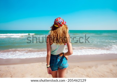 Outdoor fashion portrait of young sensual happy woman  in stylish colored  swag hat and  jeans shorts .Enjoying summer vacation. - stock photo