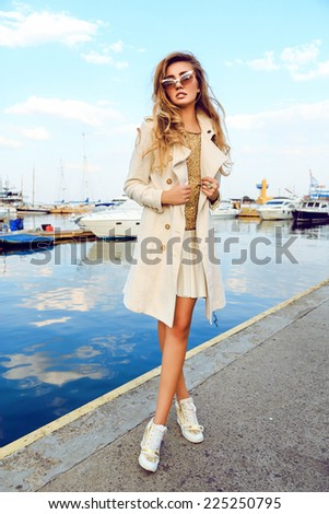 Outdoor fashion portrait of young sexy blonde woman, posing at sea port in trendy cashmere coat, golden top and sunglasses, amazing view on the sea, nice sunny fall autumn day. - stock photo