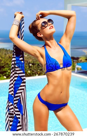 Outdoor fashion portrait of young sexy model woman with perfect slim fit tanned body, enjoy her summer vacation on luxury villa, amazing view on pool and island ocean, wearing bikini and sunglasses. - stock photo