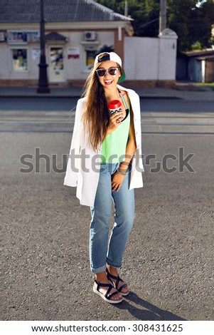 Outdoor fashion portrait of young teen hipster girl, street style swag look, hat, mom jeans, neon colors, travel at Europe.