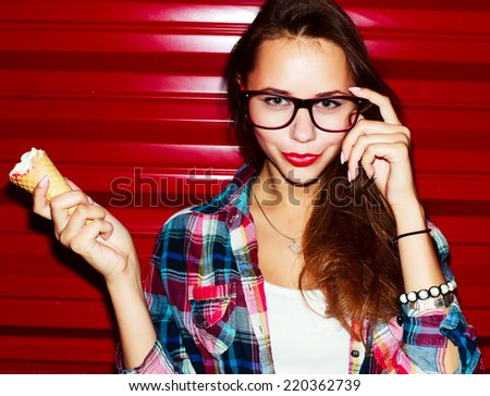 Outdoor fashion stunning closeup  portrait of pretty attractive nice girl with red lips ice-cream and glasses posing on red vivid color urban background  - stock photo