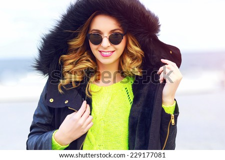 Outdoor fashion winter portrait of pretty stylish woman wearing neon sweater, stylish warm parka and sunglasses, have amazing smile and curled hairs. Bright colors. - stock photo