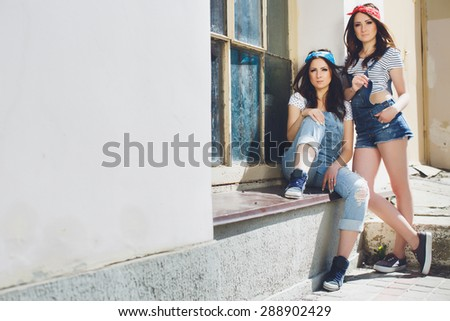 Outdoor fashionable portrait of two young attractive gorgeous twins girls wearing retro overalls and bandanas. One sitting on the windowsill, another girl standing near, both are looking at the camera - stock photo