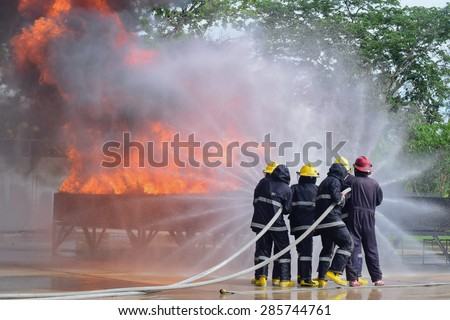 outdoor fire fighter training use two water line for extinguish a fire and protect team - stock photo