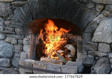 Outdoor fireplace with burning fire in a cold day. horizontal view