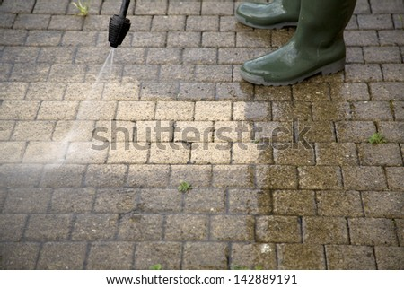 Outdoor floor cleaning with high pressure water jet - stock photo