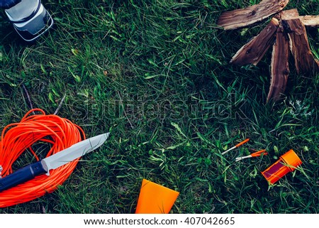 Outdoor food items set. Travel, tourism and camping equipment. Picnic rest, cooking gear on the nature. Summer BBQ and grill tools. Campfire, knife, light and rope on grass. Exploring and survival. - stock photo