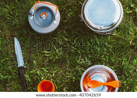 Outdoor food items set. Travel, tourism and camping equipment. Picnic rest, cooking on the nature. Summer BBQ and grill tools. Campfire kettle with tea or coffee, knife, cup and plate on grass. - stock photo