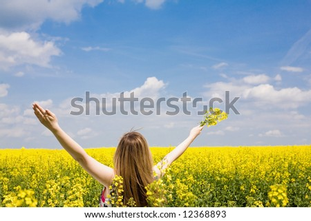 Outdoor freedom / Woman spreading her arms in the middle of a rapeseed field - stock photo