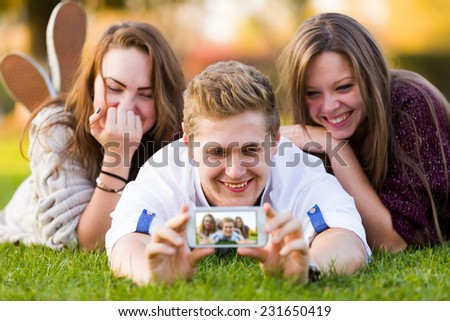 Outdoor fun with friends using technology for social networks. - stock photo