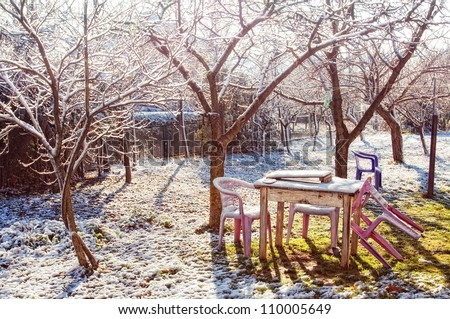 Outdoor garden and table set with a dusting of snow. - stock photo