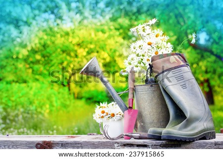 Outdoor gardening tools and flowers/ Spring Gardening tools and a straw hat on beautiful garden background - stock photo