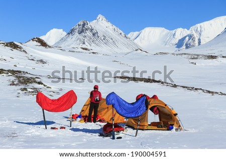 Outdoor gear and sleeping bags drying at a campsite in the snow. - stock photo