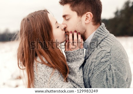 Outdoor happy couple in love posing in cold winter weather. Young boy and girl having fun outdoor - stock photo