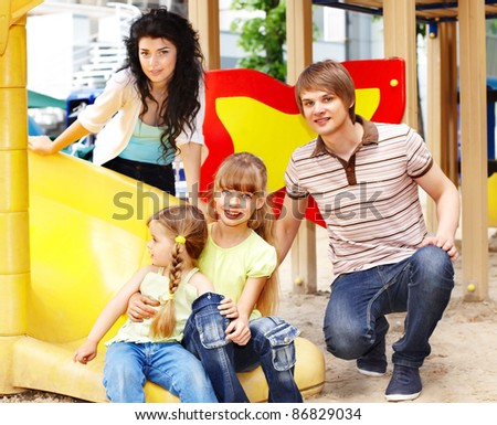 Outdoor happy family with children on slide.