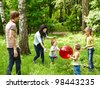 Outdoor happy family with children plaing ball  on green grass. - stock photo