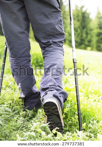 Outdoor Hiker with Trekking Poles and Equipment Walking in the Forest - stock photo