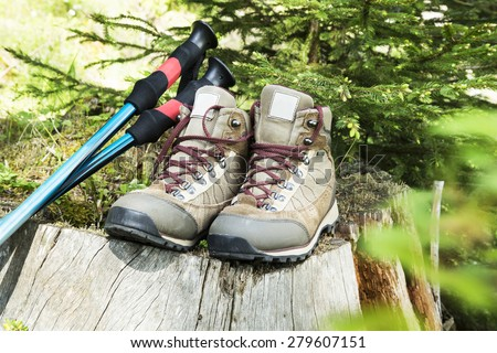 Outdoor Hiking and Trekking Boots and Poles in the Forest - stock photo