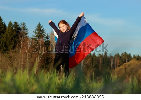 Outdoor image of lovely patriotic little girl holding Russian flag over beautiful Russian nature - stock photo